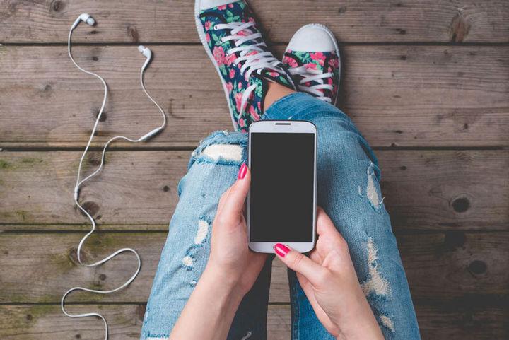 Ungdom som sit med ein mobiltelefon på fanget