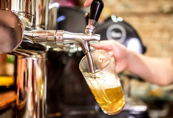 barman hand at beer tap pouring a draught lager beer serving in