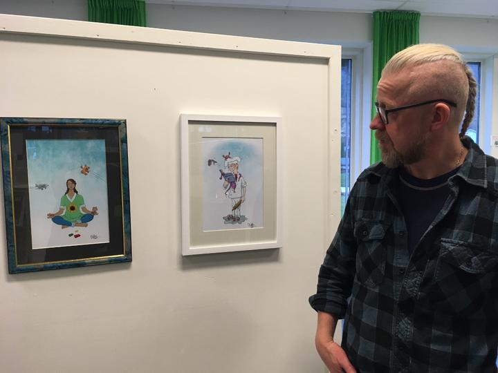 Illustratør Olav Arild Barsnes ser på to av bilda sine