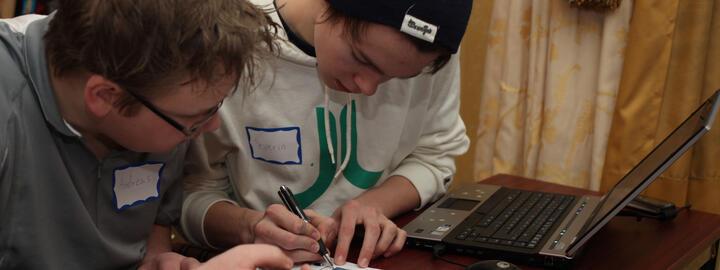 Foto av to unge gutar som sit og jobbar konsentrert ved ein pc. Dei har namnelappar det står Andreas og Severin på. Den eine har svart lue, den andre briller.