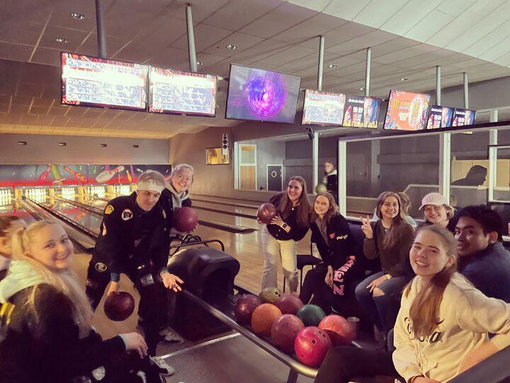 Ungdommar med bowlingkuler i bowlinghall