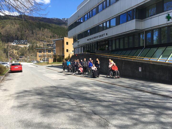 ei gruppe ungdom som triller rullestolar med eldre