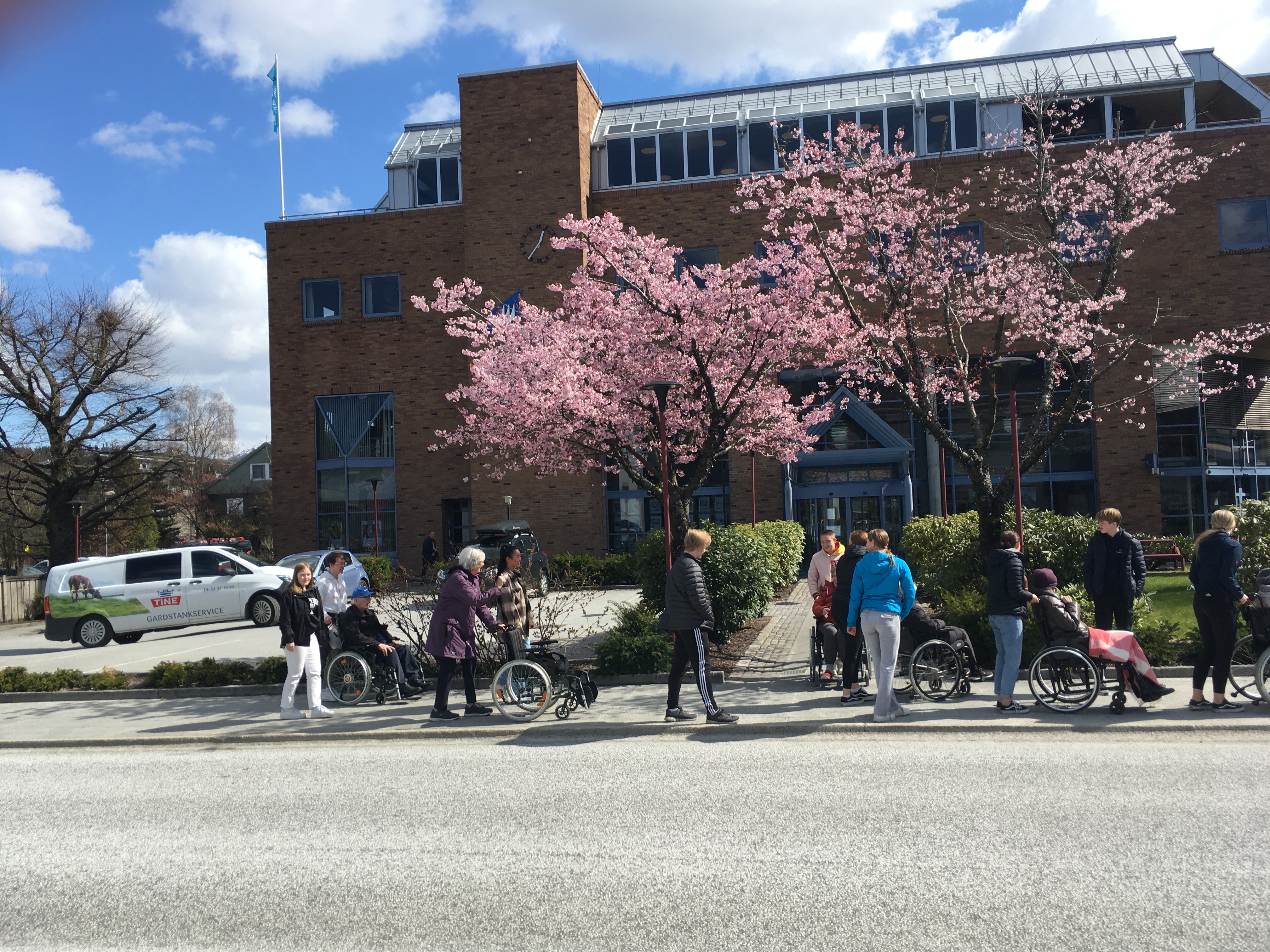 Ei gruppe ungdom som triller rullestolar med eldre forbi banken