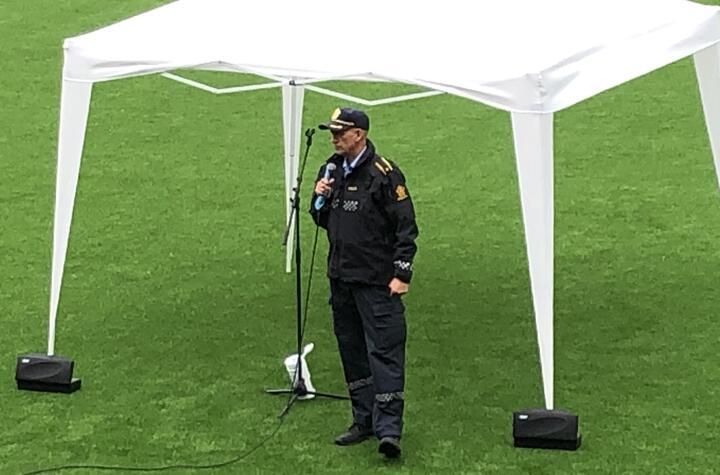Bilete syner Politi i uniform, ståande på fotballbana, som informerer elevar ved skulestart