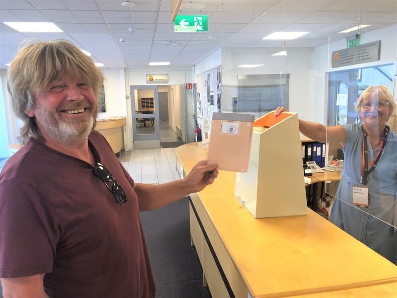 Jan Arild Karlsen leverer stemmeseddelen mens Britt Pedersen passer på at legitimasjonen er i orden.