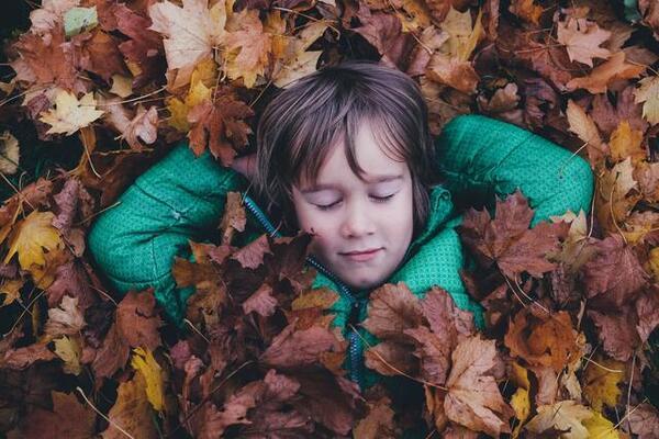Barn hviler i høstløvet