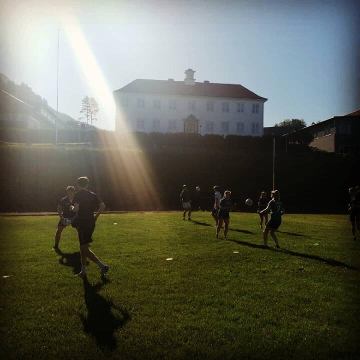 Bilde av skulen og elevar som spelar fotball.