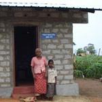 Kvinne og barn foran nytt hus